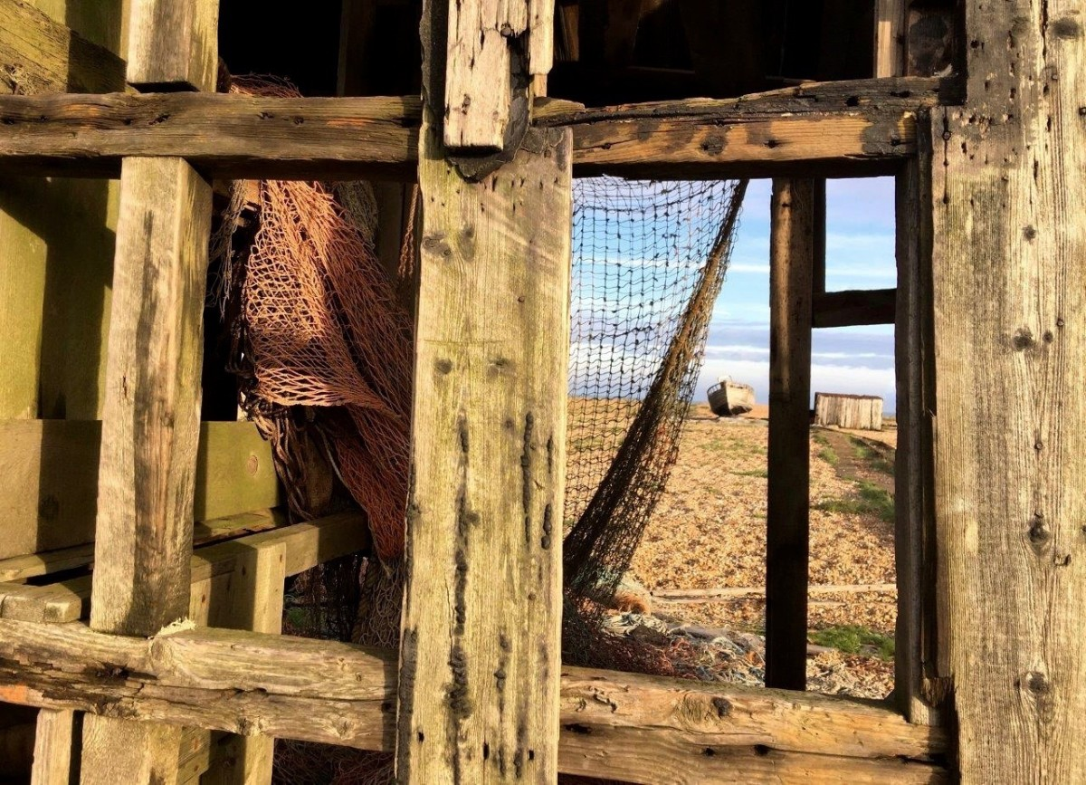 Dungeness Kent UK view through abandoned shack of boat and shingle beach with Seen by Solomon travel blog