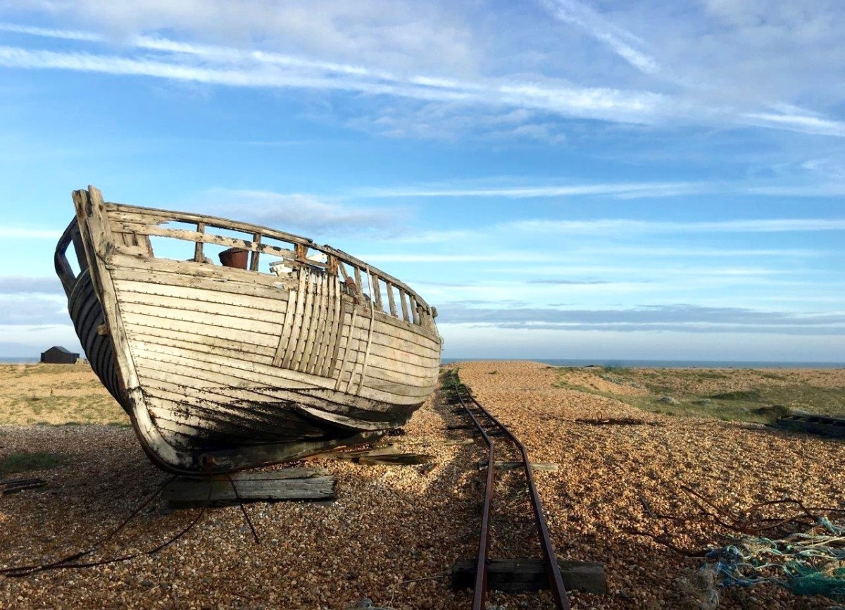 Dungeness Kent UK abandoned boat and rusty track on shingle beach with Seen by Solomon travel blog