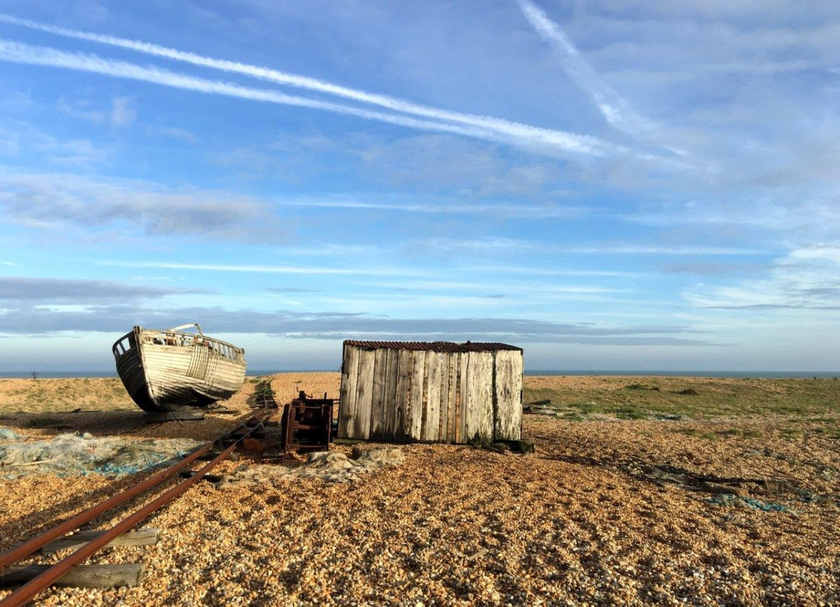 Dungeness Kent UK abandoned shack and boat on shingle beach with Seen by Solomon travel blog