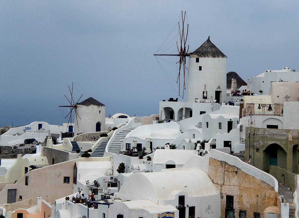 Oia in Santorini Greece view of buildings and windmills with Seen by Solomon travel blog