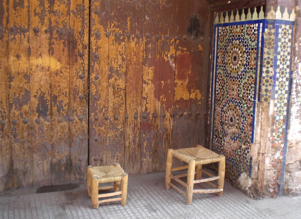 Marrakech, Morocco, huge old doorway with traditional stools and mosaics with Seen by Solomon travel blog